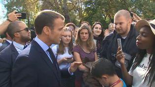 Emmanuel Macron discute avec un chômeur dans les jardins de l'Elysée, à Paris, à l'occasion des Journées du patrimoine, le 15 septembre 2018. (POOL / FRANCETELEVISIONS)