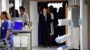 Emmanuel Macron dans un couloir de l'hôpital de la Pitié Salpêtrière, à Paris, le 27 février 2020. (MARTIN BUREAU / AFP)