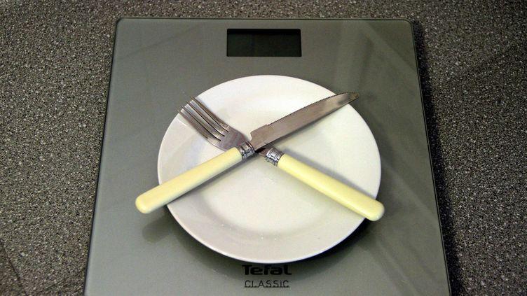 Des couverts et une assiette vide sur une balance. (MAXPPP)