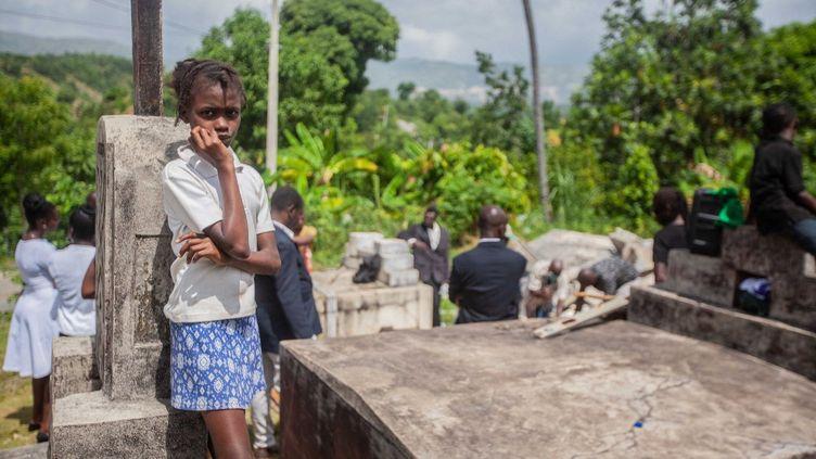 Une jeune fille assiste aux funérailles de deux victimes du tremblement de terre à Marceline, en Haïti, le 24 août 2021. (RICHARD PIERRIN / AFP)
