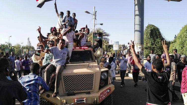 Des manifestants soudanais font le V de la victoire sur le capot d'un véhicule militaire le 7 avril 2019 à Khartoum. (AFP)