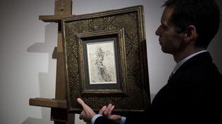 Un employé de la maison d'enchères Tajan présente, le 3 décembre 2016 à Paris, un dessin représentant Saint Sébastien, attribué à Léonard de Vinci. (PHILIPPE LOPEZ / AFP)