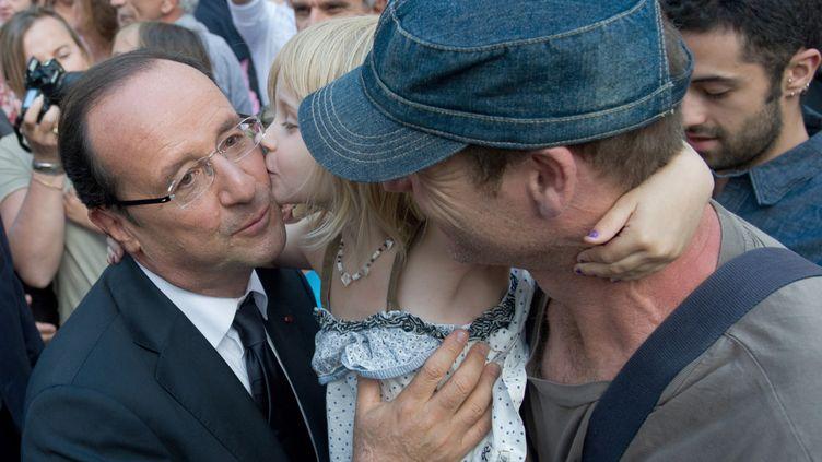 """""""Je suis le président des bisous"""", a déclaré François Hollande, lors de la visite d'une école, en juin. Dans les premières semaines de son mandat, en effet, le président n'a cessé de recevoir des baisers d'encouragement. (BERTRAND LANGLOIS / AFP)"""