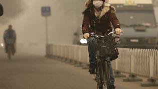Pour se protéger de la pollution, les Pékinois sont invités à porter un masque avec filtre. (STEPHEN SHAVER / MAXPPP)