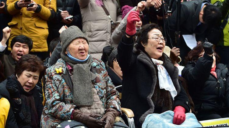Elles protestent contre l'accord intervenu entre Séoul et Tokyo, présenté comme «historique», pour régler le différend sur celles qu'on appelait des «femmes de réconfort». Selon cet accord, le Japon a offert des «excuses sincères» et un milliard de yens (7,5 millions d'euros) aux 46 Sud-Coréennes, encore vivantes, qui furent il y a 70 ans contraintes de se prostituer pour les militaires japonais. Outrées, les femmes comme Lee Yong-Soo et Gil Won-Ok affirment vouloir se battre jusqu'à ce que le Japon endosse la responsabilité officielle des atrocités commises, afin de rendre justice aux victimes décédées. Salué par Washington, l'accord est dénoncé en revanche par la presse chinoise qui juge insuffisantes les excuses japonaises. (AFP PHOTO / JUNG YEON-JE  )