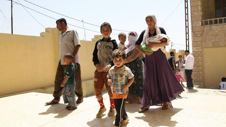 Des irakiens de la minorité Yezidi fuient leur ville de Sinjar, le 4 août, avant l'arrivée des jihadistes. La majorité d'entre eux a gagné une montagne voisine, où 40 enfants sont morts deshydratés ces derniers jours. (STRINGER IRAQ / REUTERS)