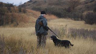 Un chasseur et son chien dans la campagne. (MIKE KEMP / CORBIS HISTORICAL/ GETTYIMAGES)