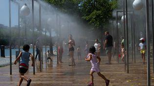 Des enfants jouant dans des brumisateurs publics à Paris (PATRICIA MORIBE / HANS LUCAS / AFP)