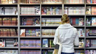 400 auteurs de BD signent une pétition dans Libération contre la précarisation de leur profession. Ci-contre, une jeune fille regarde des mangas lors du 43e Festival d'Angoulême en janvier 2016. (GEORGES GOBET / AFP)