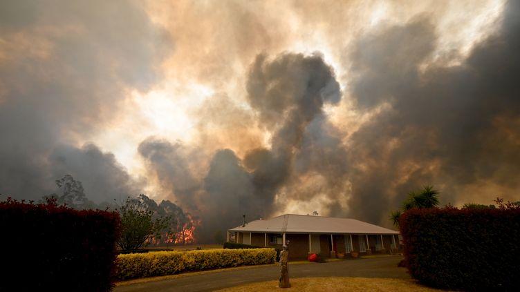 Des arbres brûlentderrière une propriété à Balmoral, à 150 kilomètres au sud-ouest de Sydney, le 19 décembre 2019. (PETER PARKS / AFP)