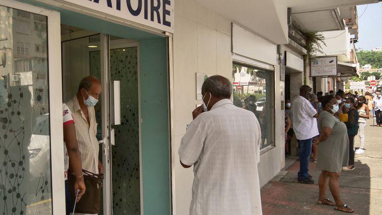Des habitants de la Martinique devant un laboratoire à Fort-de-France. (THOMAS THURAR / AFP)