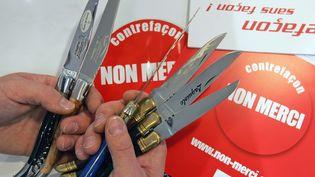 """22 août 2006 à Laguiole (Aveyron), de deux """"vrais"""" couteaux Laguiole (G) exposés près de quelques faux fabriqués en Chine et au Pakistan. Sur la lame effilée est inscrit """"Laguiole garantie"""". (ERIC CABANIS / AFP)"""