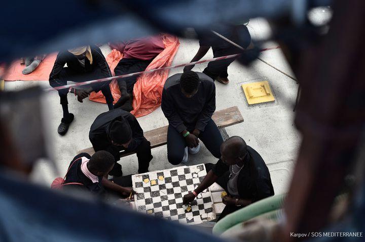 Des migrants en train de jouer aux dames, vendredi 15 juin 2018, à bord de l'Aquarius. (KARPOV / SOS MEDITERRANEE)