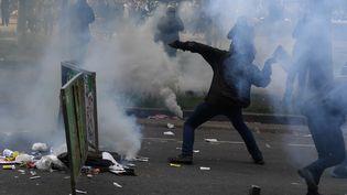 Un homme lance un projectile en direction de policiers en marge du défilé du 1er-Mai à Paris, le 1er mai 2018. (ALAIN JOCARD / AFP)