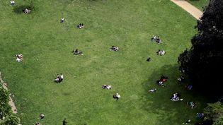 Des gens sont étendus sur la pelouse d'un parc parisien le 6 juin 2016, un jour ensoleillé. (JACQUES DEMARTHON / AFP)