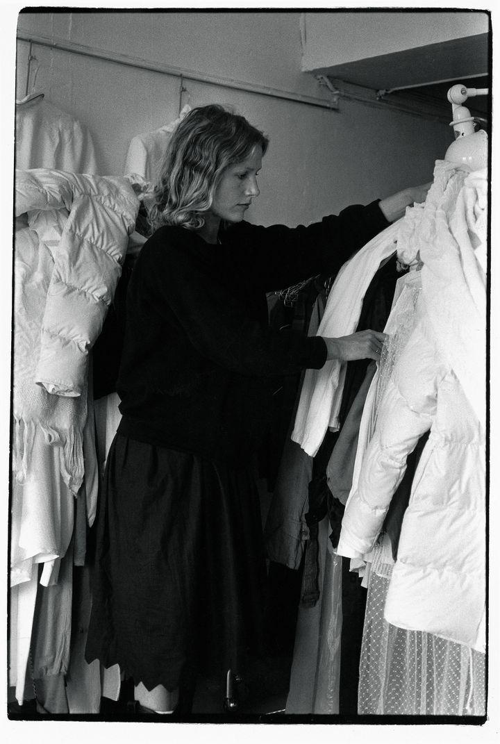 Agnès porte un sweat et un jupon cranté en coton noir de sa collection hiver 1979. Elle choisit parmi les doudounes en anti-‐duvet de coton, les chemises et jupons blancs, ceux qui vont être teints.   (Archives Agnès b. / DR)