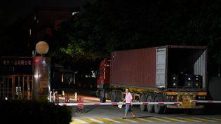 Un ouvrier passe devant l'entrée d'une entreprise de fabrication de produits électroniques d'apprentissage à Houjie, dans le sud de la Chine,une zone touchée par des restrictions d'électricité,le 30 septembre 2021. (NOEL CELIS / AFP)