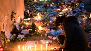 Un adolescent allume une bougie en hommage à Samuel Paty, enseignant assassiné à Conflans-Sainte-Honorine, le 17 octobre 2020. (BERTRAND GUAY / AFP)
