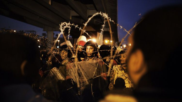 Des policiers égyptiens se pressent derrière des barbelés pendant une manifestation de militants hostiles au pouvoir militaire, le 10 février au Caire. (MARCO LONGARI / AFP)