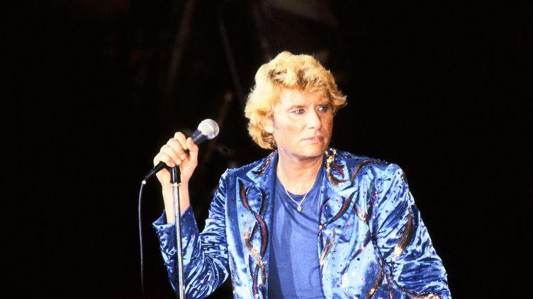 Les vêtements bleus et la crinière blonde, Johnny chante devant son public à Paris, le 15 septembre 1982. (KEYSTONE-FRANCE / GAMMA-KEYSTONE / GETTY IMAGES)