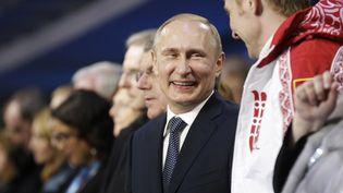 Le président russe, Vladimir Poutine, discute avec le double champion olympique de bobsleighAlexandre Zubkov, le 23 février 2014, lors de la cérémonie de clôture des JO d'hiver de Sotchi (Russie). (DAVID GOLDMAN / AFP)
