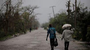 Des habitants de Cayes (Haïti) longent la route après le passage de l'ouragan, le 4 octobre 2016 (ANDRES MARTINEZ CASARES / REUTERS)