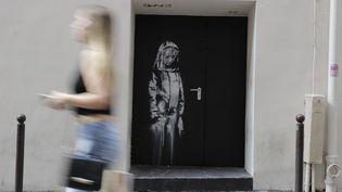 L'oeuvre de Banksy sur une porte de secours du Bataclan  (Thomas SAMSON / AFP)