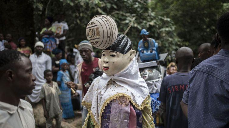 Un homme masqué porte un costume gèlèdé, lors du festival Osun-Osogbo à Osogbo. Des milliers de personnes assistent au festival annuel Osun-Osugbo pour célébrer Osun, grande déesse yoruba de la fertilité et de l'eau. Comme chaque année depuis 32 ans, la prêtresse Osundele Okugbesan a rejoint, au bois et à la rivière sacrés d'Osogbo, la foule immense de fidèles et de prêtres pour célébrer la divinité.  «Je suis habillée en rivière», dit-elle en montrant sa grande robe bustier blanche, qui flotte sur ses jambes, et ses longs colliers de perles, qui tombent sur sa poitrine. D'autres femmes de sa congrégation, qui l'accompagnent, ont cousu des coquillages à leur robe brodée, ou se sont tatoué des poissons sur le corps. Sur la rive, à l'ombre des arbres centenaires de la forêt sacrée, classée au Patrimoine mondial de l'humanité depuis 2005, une femme lit l'avenir dans les noix de kola, pendant que des centaines de personnes viennent récupérer de l'eau dans des bidons en plastique. D'autres femmes, en transe, doivent être tenues de force pour ne pas qu'elles se noient en s'offrant à la rivière. Ni les djihads successifs des musulmans venus du Sahel, ni les missionnaires chrétiens portugais puis anglais, ni même les récents pasteurs évangélistes, ne sont parvenus à étouffer la croyance en la belle Osun et en ses pouvoirs surnaturels, notamment celui d'aider les femmes à tomber enceintes.          ( STEFAN HEUNIS / AFP)
