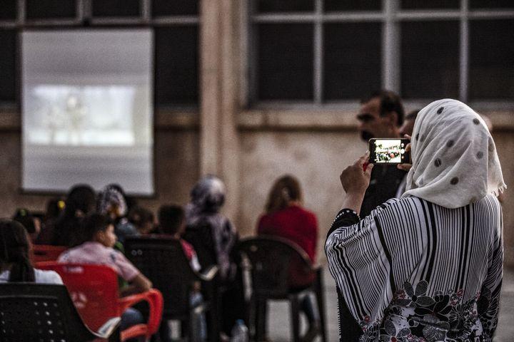 Une femme prend une photo de l'assemblée de spectateurs pendant une séance du cinéma itinérant à Shaghir Bazar, dans le Nord-Est de la Syrie. (DELIL SOULEIMAN / AFP)