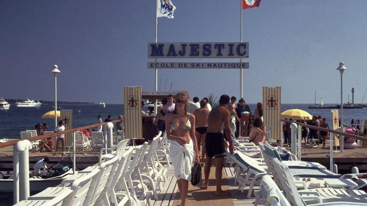 Des vacanciers sur la plage de l'hôtel Majestic à Canne le 27 juin 2014. (NEIL SETCHFIELD / THE ART ARCHIVE / AFP)
