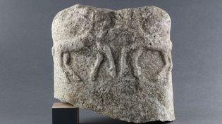 Un fragment de statue de style celtique représentant un torse humain. Au dos sont sculptés deux animaux en plein combat. (© Mathilde Noel, Inrap)