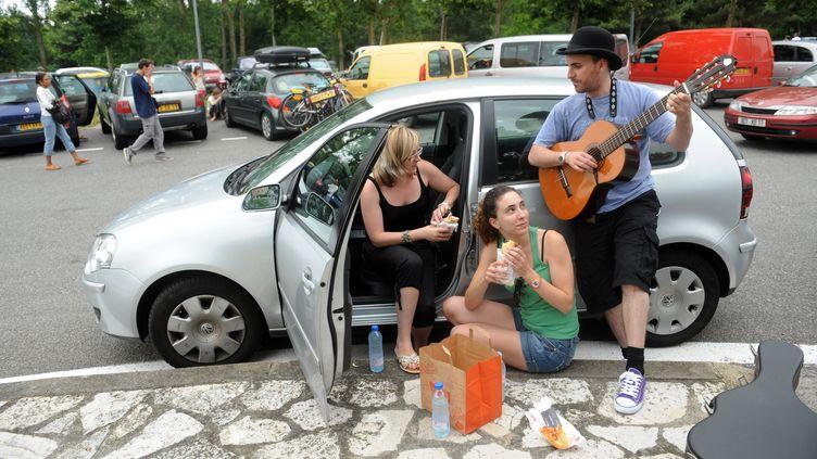 Des automobilistes sur la route des vacances font une pause musicale, le 03 juillet 2010, sur une aire de repos de l'Autoroute des Deux Mers, entre Toulouse et Carcassonne. L'heure des grands départs a sonné le 02 juillet 2010 pour les millions de Français qui entament ce week-end leurs vacances d'été. (REMY GABALDA / AFP)
