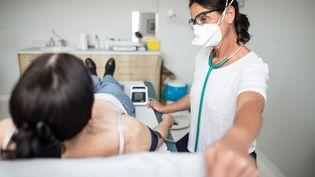 Une patiente auscultée par sa médecin généraliste, le 30 mars 2020, à Roanne (Loire). (VERONIQUE POPINET / HANS LUCAS)