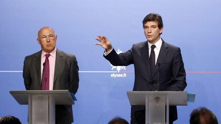 Le ministre du Travail Michel Sapin (à g.) et le ministre du Redressement productif Arnaud Montebourg à l'Elysée, à Paris, le 25 juillet 2012. (REMY DE LA MAUVINIERE / AFP)
