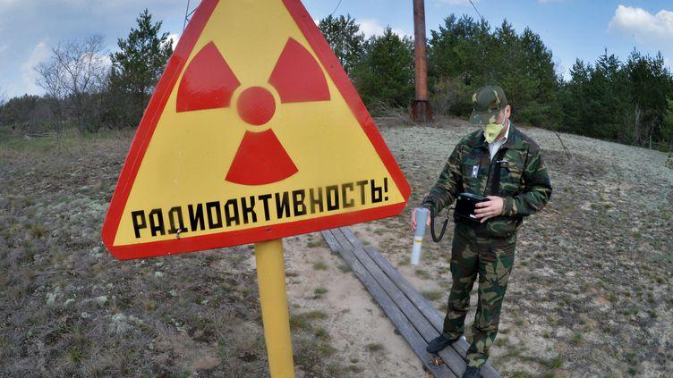 Un homme mesure les radiations dans la zone d'exclusion de Tchernobyl en Biélorussie. (VIKTOR TOLOCHKO / RIA NOVOSTI)