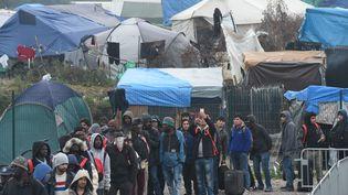 """Des migrants attendent à l'entrée du """"sas"""" prévu pour les orienter, pendant l'évacuation de la """"jungle"""" de Calais, le 24 octobre 2016, à Calais. (FRANCOIS LO PRESTI / AFP)"""