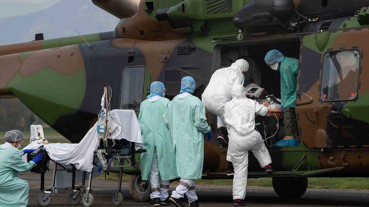 Lepersonnel médical décharge deux patients atteints de la maladie Covid-19 à leur arrivée à bord d'un hélicoptère NH90 Caiman du 1er RHC à l'aéroport de Grenoble Le Versoud,le 29 mars 2020. (HANDOUT / MINISTERE DES ARMEES)