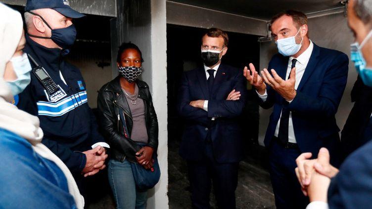 Emmanuel Macron et le maire de Montpellier, Michaël Delafosse, lors d'un échange avec des habitants du quartier de La Mosson, à Montpellier (Hérault), le 19 avril 2021. (GUILLAUME HORCAJUELO / AFP)