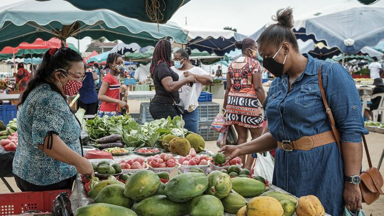 Une femme portant un masque de protection contre le Covid-19 achète des fruits et légumes au marché de Saint-Laurent du Maroni, en Guyane, le 13 juin 2020. (JODY AMIET / AFP)