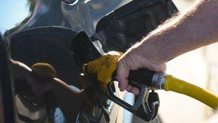 Un hommes'approvisionne encarburant dans une station-service de Caen (Calvados), le 17 juillet 2019. (ARTUR WIDAK / NURPHOTO / AFP)