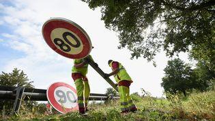 Des employés de la DIR replacent un panneau de limitation des 90 km/h à Wittenheim (Haut-Rhin), le 1er juillet 2018. (SEBASTIEN BOZON / AFP)