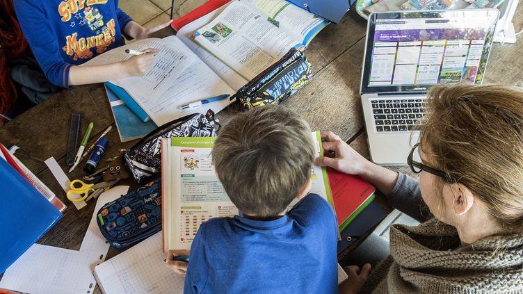 Une mère de famille encadre le travail scolaire de ses enfants, le 27 mars 2020. (MAXPPP)