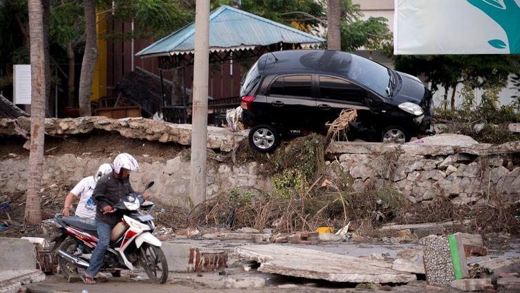 Un homme tente de conduire sa moto à Palu, sur l'île des Célèbes en Indonésie, le 29 septembre 2018. La veille, un séisme et un tsunami ont frappé l'île. (BAY ISMOYO / AFP)
