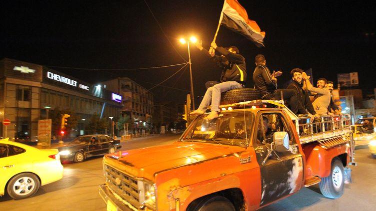 Des Irakiens célèbrent la fin du couvre-feu à Badgad, dans la nuit du 7 au 8 février 2015. (ALI AL-SAADI / AFP)