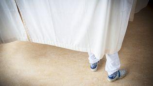 Une infirmière derrière le rideau d'une chambre d'hôpital, en 2013. (ARNO MASSEE / SCIENCE PHOTO LIBRARY / AFP)