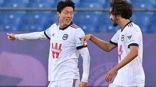 De gauche à droite : Ui-Jo Hwang et Yacine Adli lors du match des Bordelais contre Montpellier, le 22 septembre 2021. (PASCAL GUYOT / AFP)