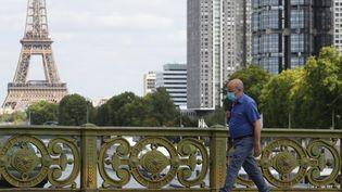 Un homme porte un masque sur le pont Mirabeau, près de la Tour Eiffel, à Paris, le 27 août 2020 (photo d'illustration). (LUDOVIC MARIN / AFP)