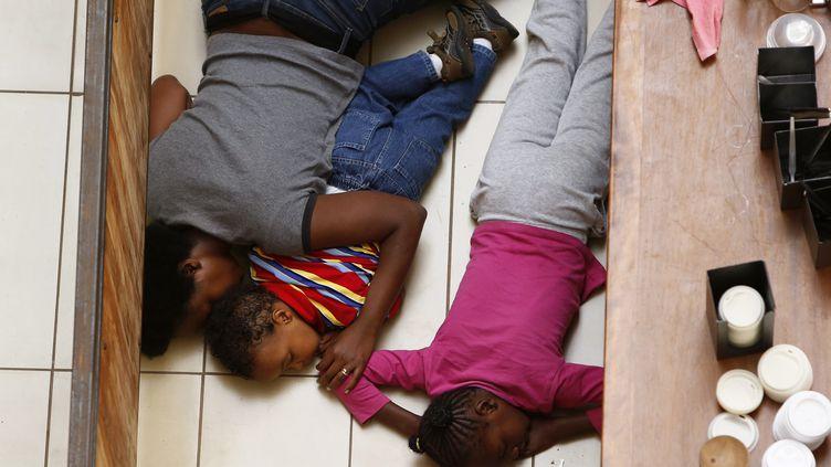 Une mère et ses deux enfants se cachent pendant l'attaque terroriste contre le centre commercial Westgate à Nairobi au Kenya le 22 septembre 2013. (REUTERS)