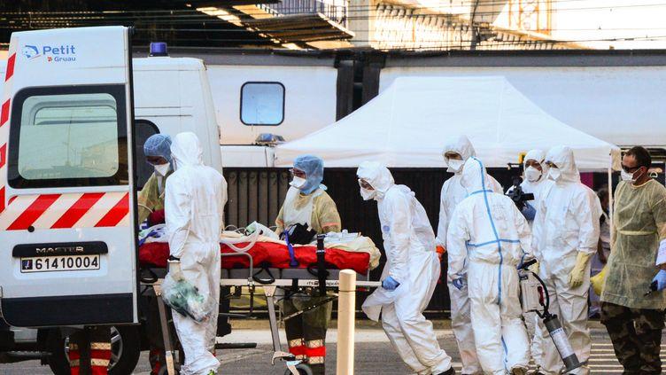 Un patient atteint de Covid-19 est embarqué à bord d'une ambulance, le 10 avril 2020 à Bordeaux (Gironde). (MEHDI FEDOUACH / AFP)