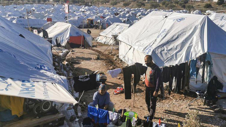 Un couple de migrants étend son linge à l'extérieur de sa tente, dans le camp de réfugiés de Kara Tepe, sur l'île de Lesbos (Grèce), le 19 décembre 2020. (ANTHI PAZIANOU / AFP)